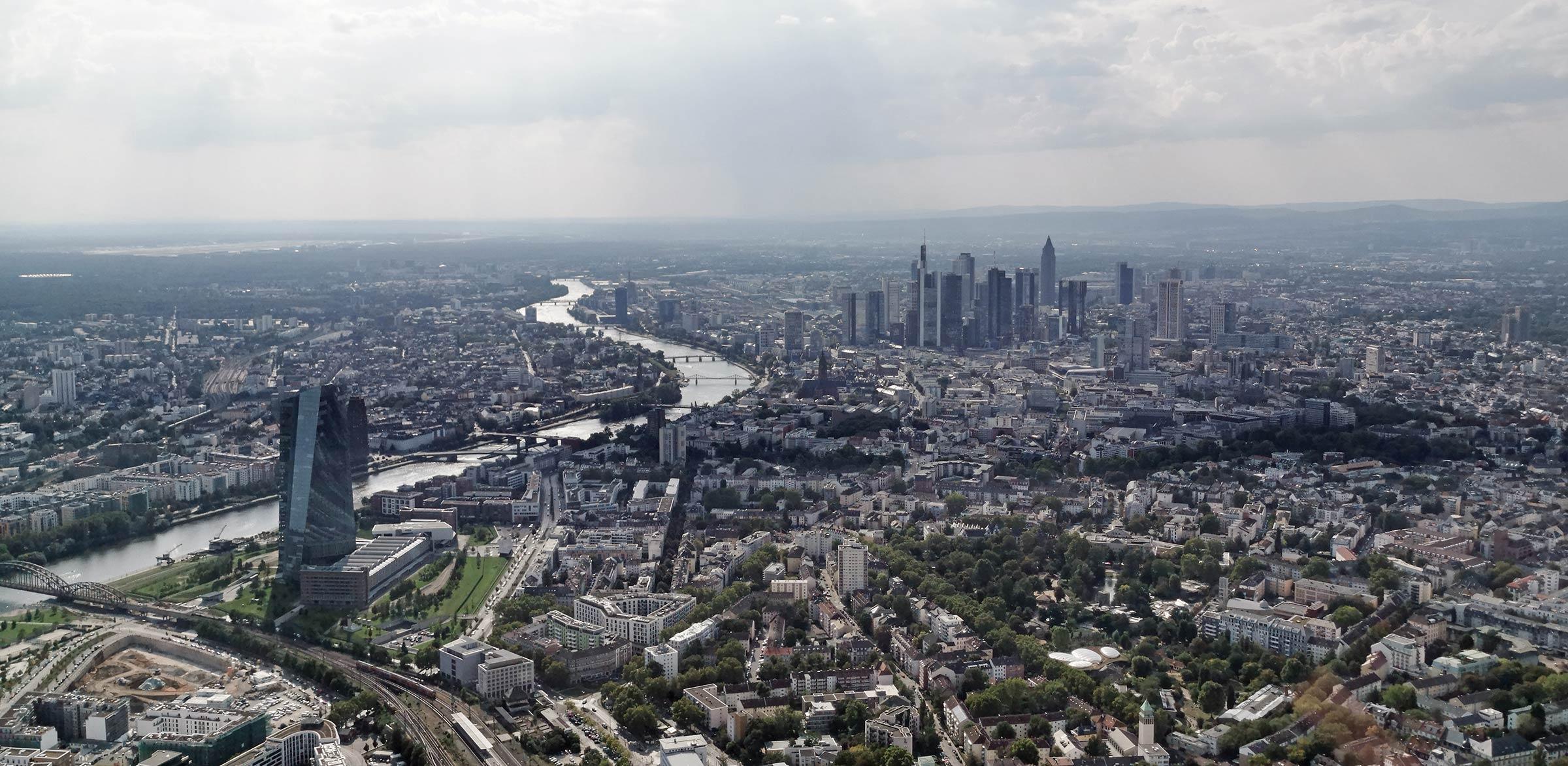 EZB links im Bild - Die europäische Zentralbank mit Blick auf die Hochhäuser im Frankfurter Bankenviertel