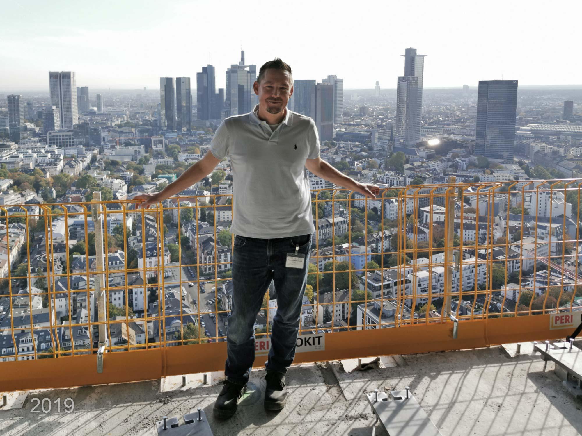 Michael Wutzke bei einer Baustellenbesichtigung in einem Hochhaus mit Blick auf die Frankfurter Skyline