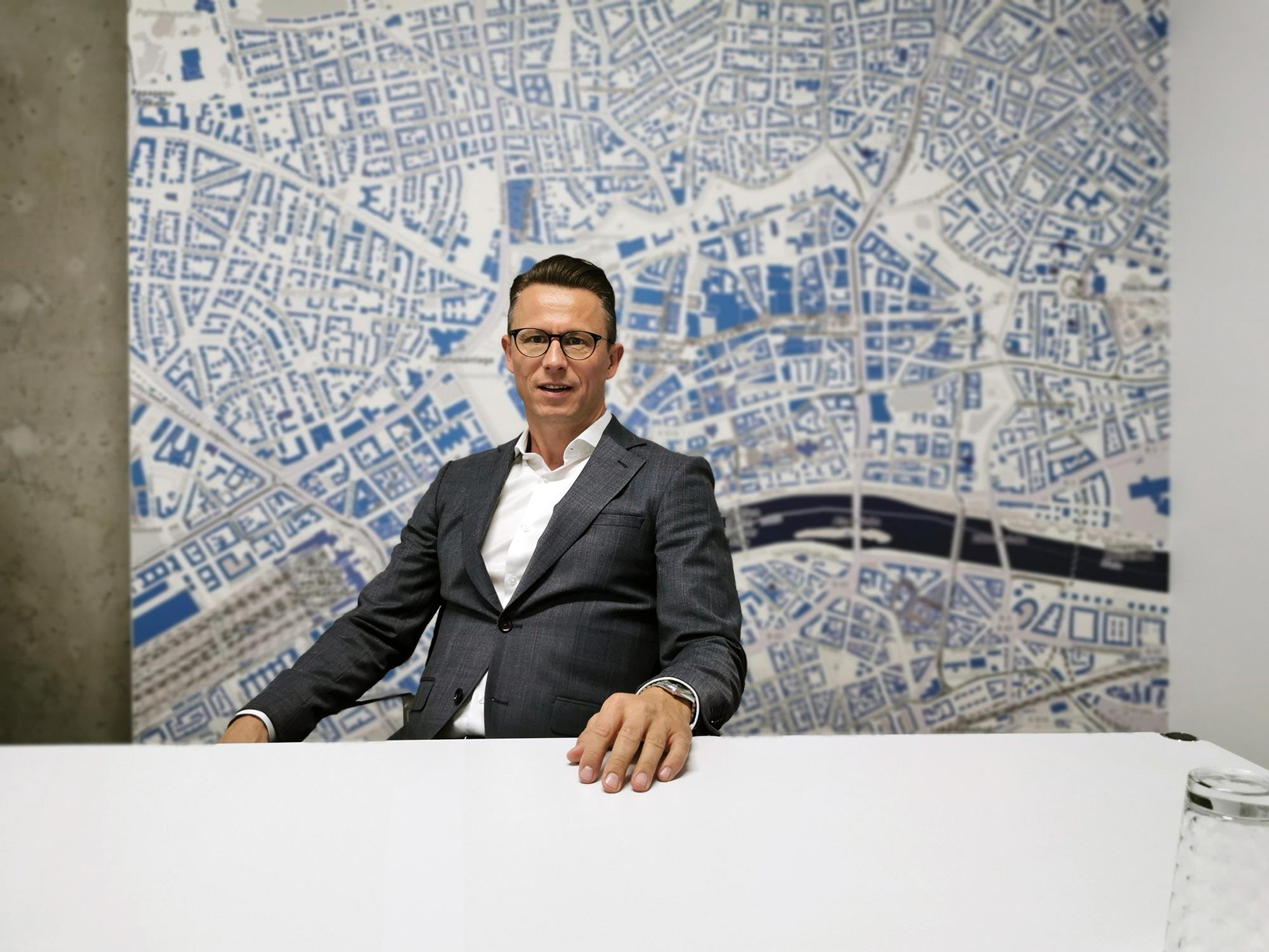 Immobilienmakler Frankfurt - Dean Vukovic vor einem Stadtplan der Frankfurter Innenstadt